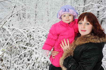 Young beautiful mother with little daughter stands in woods in snow photo