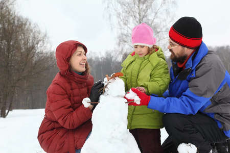 Mother and dad of squatting alongside with daughter and sculpt snowman photo