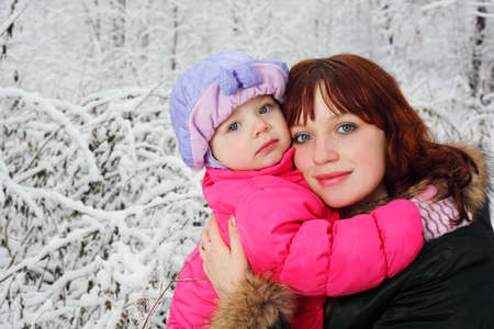 Young beautiful mother hugs little daughter in woods in snow at winter photo