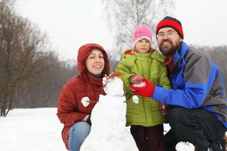 three day beard: Father with mother of squatting alongside daughter and snowman and smile