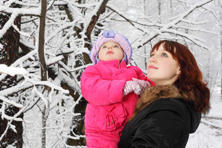 Young beautiful mother with little daughter look up in woods in snow at winter photo