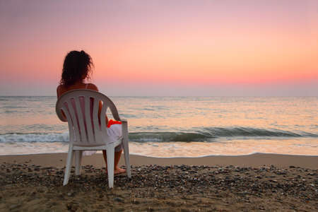 beautiful young woman sitting on white plastic chair on beach\ and watching sunset, shallow depth of Focus