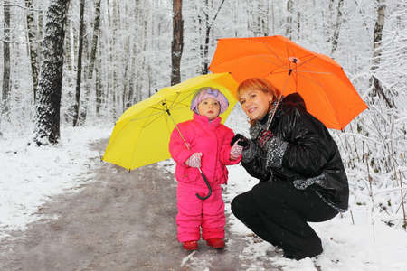 Grandmother and little granddaughter with yellow and orange umbrella stand in woods in snow photo