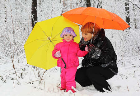 Grandmother and granddaughter with yellow and orange umbrella stand in woods in snow at winter photo