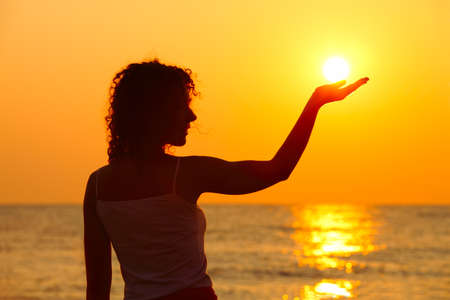 beautiful young woman standing on beach, watching sunset, holding  sun in hand