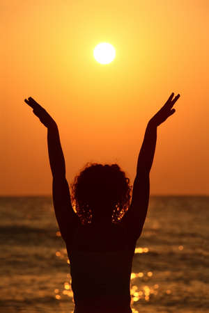 raises: beautiful young woman standing on beach, watching sunset, raises her hands