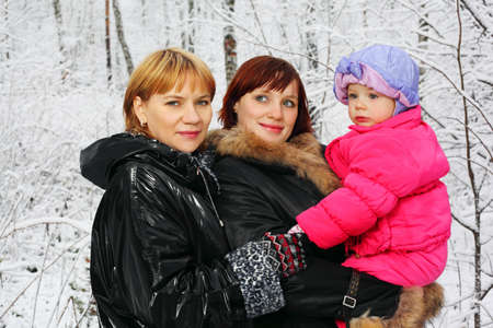 Grandmother, young mother and little daughter stand in woods in snow at winter photo