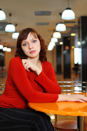 deplorable: Young girl sorrowful dressed in red blouse sitting in empty cafe