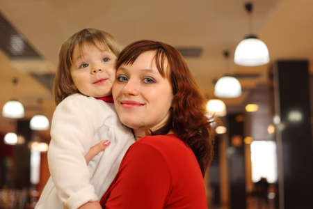 Young mother with little smiling daughter stand in empty cafe photo