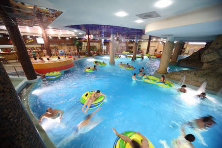 aquapark: MOSCOW - MARCH 21: People swim on inflatable circles in pool and in jacuzzi in Kva Kva park  on March 21, 2010 in Moscow , Russia. Most skilled masseurs and bathhouse attendants are glad to offer you services. Editorial