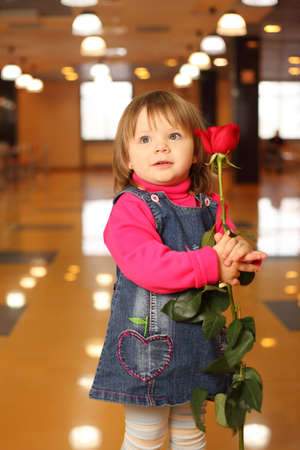 Little beautiful girl with red rose in hands stand in empty cafe photo