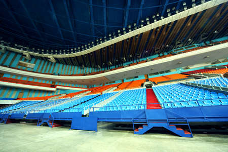 prospect: many rows of red and blue empty plastic seats of grandstand at large stadium Editorial