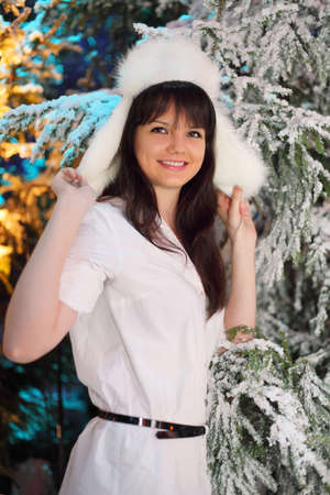 furskin: Smiling young woman wearing white shirt and white fur hat stand near green trees in snow
