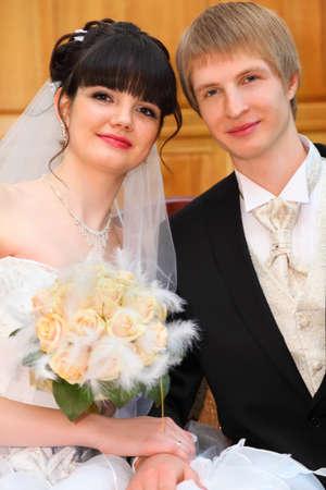 anagrafica: Sorridente sposa e lo sposo si siedono sul divano e si tengono per mano in anagrafe