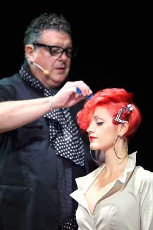 fire show: MOSCOW - SEPTEMBER 6: Tim Hartley makes hairdo for red hair model at Davines Hair Show 2010, on September 6, 2010 in Moscow, Russia.