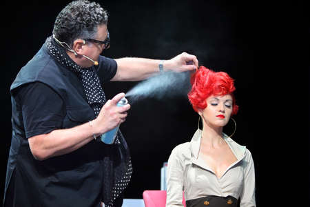 splutter: MOSCOW - SEPTEMBER 6: Tim Hartley sprays hairspray on red hair of model at Davines Hair Show 2010, on September 6, 2010 in Moscow, Russia.  Editorial