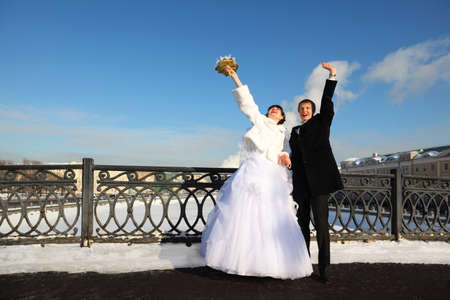 happy groom and bride shouting and waving their hands at winter outdoors, couple standing on bridge Stock Photo - 17745816