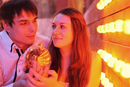 Young man and woman stand near wall with small lamps, hold Christmas ball and look at each other photo