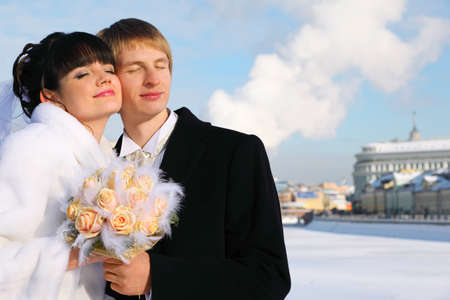 house coats: embracing smiling groom and bride with closed eyes holding bouquet of roses at winter outdoors, couple standing on bridge  Stock Photo