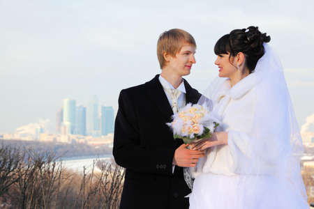 smiling groom and bride holding bouquet of roses and look at each other at winter outdoors photo