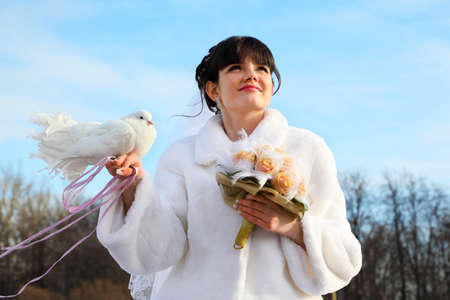 beautiful bride with bouquet holds white dove and looks into distance at winter outdoors photo