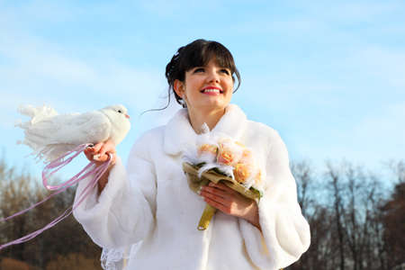 smiling bride with bouquet holds white dove and looks into distance at winter outdoors photo