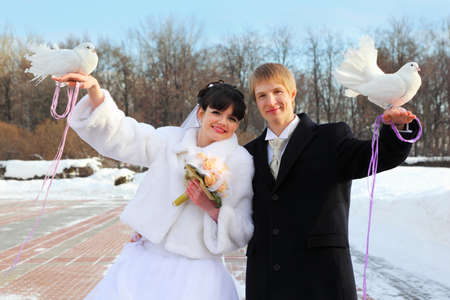 smiling beautiful bride and groom hold white doves at winter outdoors photo