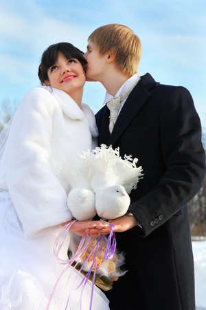beautiful bride and groom hold pair of white doves at winter outdoors; man kisses woman photo