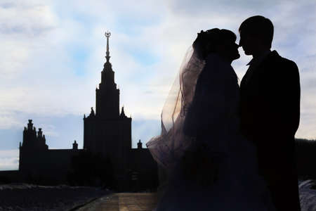 Silhouettes and profiles of bride and groom at winter outdoors, couple standing in front of Moscow State University in Moscow, Russia photo