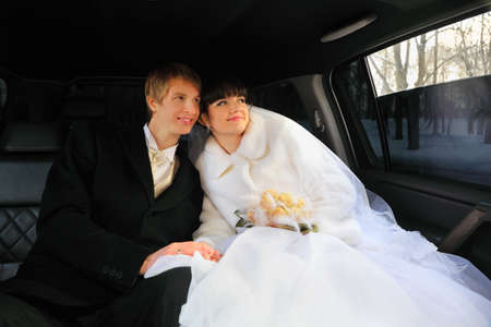 happy groom and bride with bouquet sitting inside wedding limousine and looking out window at winter photo