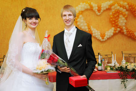 happy bride and groom stand near banquet table and keep bouquets photo