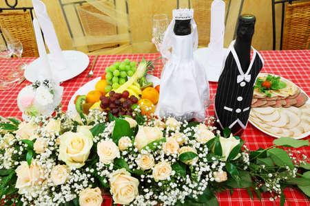 Glasses of champagne and candles: Chai rượu sâm banh mặc áo cưới đứng trên bàn lễ hội với thực phẩm và hoa Kho ảnh