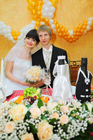 happy bride and groom sitting at banquet table and keep bouquet of roses photo