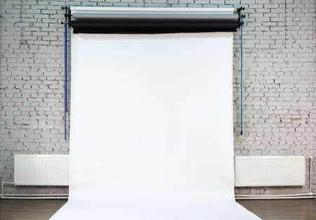 White background on white brick wall inside studio owned by photographer photo