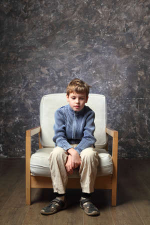 little boy sitting on white chair in studio of photographer, brown background Stock Photo - 17723222