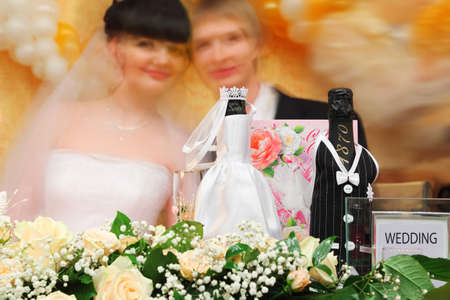 Bottles of champagne wine dressed in wedding gowns stand on festive table with flowers; Blurred faces of bride and groom in background photo
