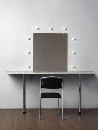 visagiste: mirror with lamps for makeup, black chair in studio, white wall Stock Photo