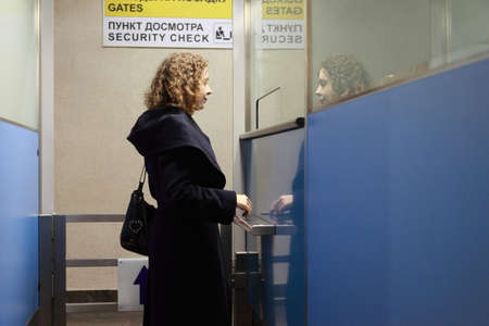 Young woman stands in the security checkpoint at the airport photo