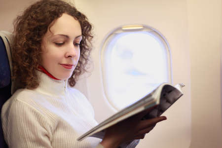 illuminator: Young woman sits in a chair near the illuminator of the airplane and reads the magazine.