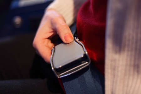 restraint device: Female hand with a lock of the seat belt, focus on the thumb, shallow depth of focus.