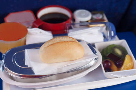 Tray of food on the plane. Focus on a bun. photo