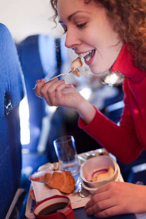 Young woman eats pancake on airplane, shallow depth of focus.