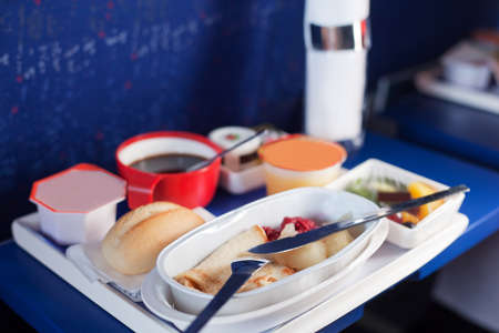 Tray of food on the plane. Focus on a plastic cruet stand with pancakes. Shallow depth of focus. Archivio Fotografico