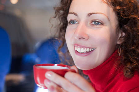 Young woman drinks coffee from the red cup on the airplane, shallow depth of focus. photo