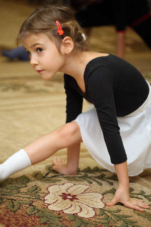 little girl in ballet class sits on string on floor with carpet photo