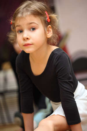 only 1 girl: little girl in ballet class sits on string on floor and looks into camera