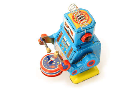 Old vintage tin robot with drum and sticks on white background photo