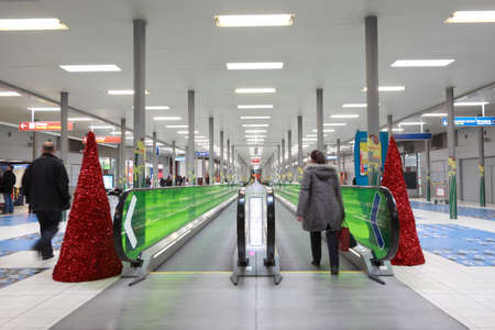 moving activity: PARIS - DECEMBER 29: Hall with horizontal escalator at the CDG airport, decorated with Christmas trees, December 29, 2009, Paris, France. This airport is the principal one of France, one of the two main airports of Paris. Editorial
