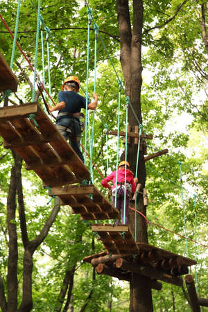 Children on course in helmet and safety equipment in rope park 스톡 콘텐츠