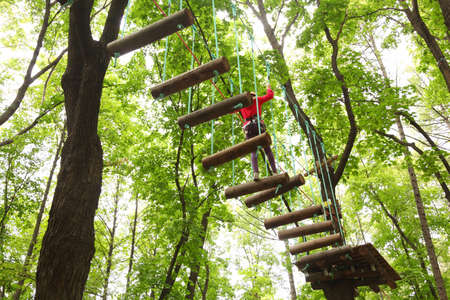 Girl wearing red shirt and helmet on course with safety equipment in rope park Standard-Bild